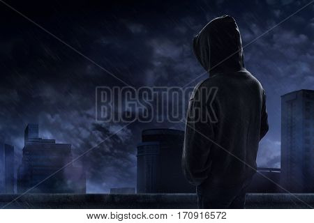 Man standing on the rooftop in a rainy night