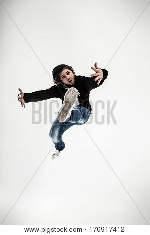 stylish rapper is dancing breakdance .photo on a white background.the rapper with headphones takes breakdancing.