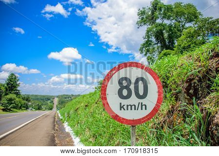 The road sign of 80 kilometres per hour limit on the background of small hill covered with green grass, long road going to horizon and blue sky with white clouds at sunny summer day