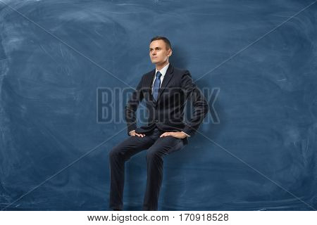 Businessman is sitting and thinking isolated on blue chalkboard background. Seeking for opportunities. Difficulties. Business planning