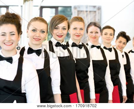 group of waiters at a prestigious restaurant standing in the column in the lobby of the restaurant
