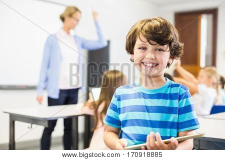 Portrait of smiling schoolboy holding digital tablet in classroom at elementary school
