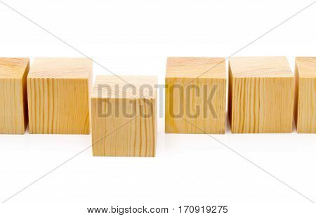 Series of brown wooden cubes with one moved forward - stepping forward or outstanding concept
