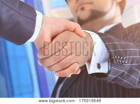 Conclusion of the transaction on the background of an office building. Handshake.