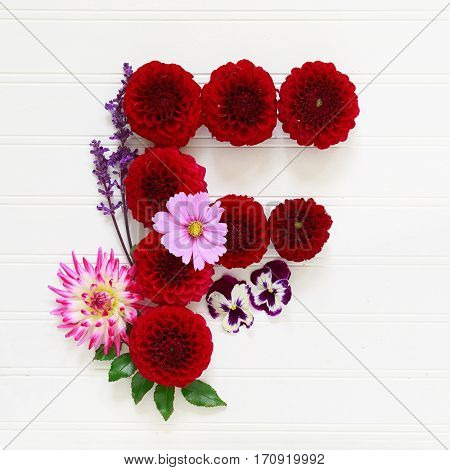 The letter F made out of garden flowers such as pansies, dahlias, cosmos, and salvia.