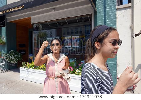 HARBOR SPRINGS, MICHIGAN / UNITED STATES - AUGUST 4, 2016: A woman eats a big bowl of Kilwin's chocolate ice cream while walking on Main Street in downtown Harbor Springs.
