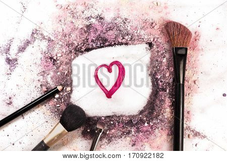 Makeup brushes, pencil and lip gloss on white marble background, with traces of powder and blush forming a frame with a heart in it. Love Makeup valentine design