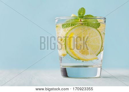 Mineral infused water with limes, lemons, ice and mint leaves on blue background. Homemade detox soda recipe.