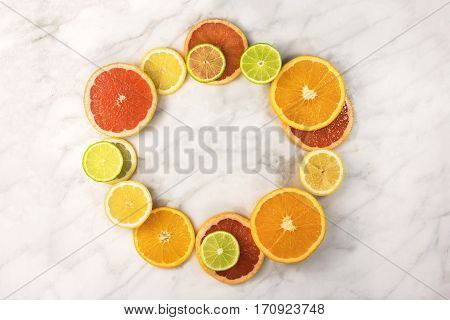 A vibrant circular frame made up of juicy citrus fruits, on a white marble texture, with copy space. Grapefruit, lime, lemon, and orange slices