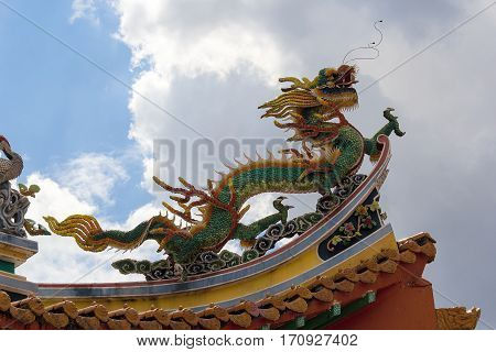 Mythical Dragon sculpture on Chinese Temple rooftop against cloudy sky