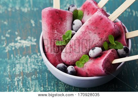 Homemade blueberry ice cream or popsicles decorated green mint leaves on teal rustic table, frozen fruit juice. Vintage style.