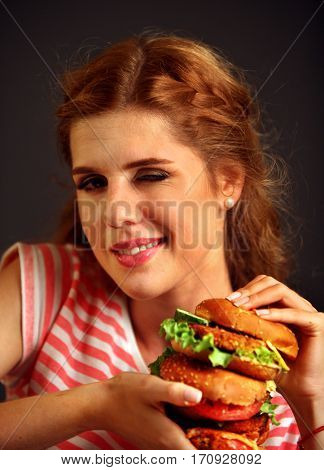Woman eating burger and winks. Happy student going to seductively eat great sandwich for lunch. Joyful woman offers fast food on black background.