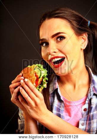 Woman eating hamburger. Girl wants to eat burger. Student consume fast food. Person with good appetite is going to have dinner delicious sandwich on a black background.