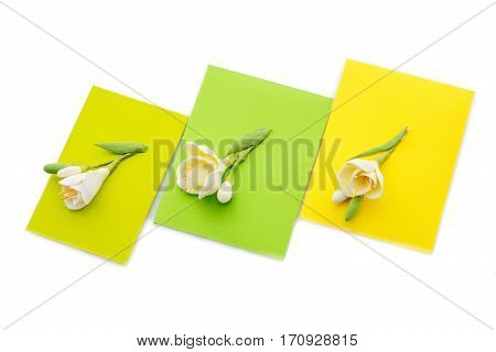 Closeup shot of three small yellow envelopes decorated with art clay tulips. Handmade paper work. Copy space. Isolated over white background.