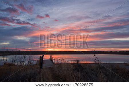 The sky bursts with color at sunrise on Lon Hagler Reservoir in Loveland Colorado