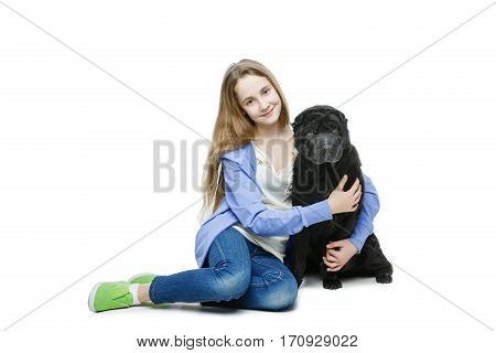 Beautiful smiling teen age girl hugging black shar pei dog. Isolated on white background. Copy space.