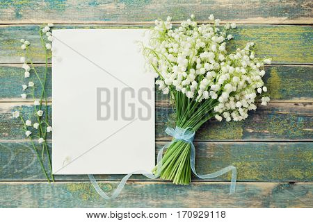 Bouquet of flowers lily of the valley and empty paper sheet on rustic table from above. Beautiful vintage card top view, copy space for text. Flat lay.