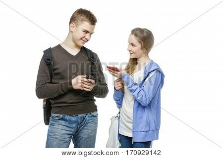 Beautiful teen age boy and girl in casual clothes holding mobile phones. School children texting using cellulars. Isolated on white background. Copy space.