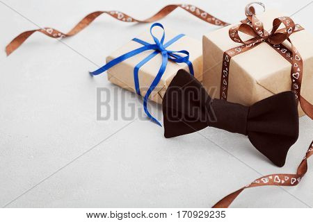 Gift or present box with ribbon and bowtie on gray desk for Happy Fathers Day, copy space for your text or design.