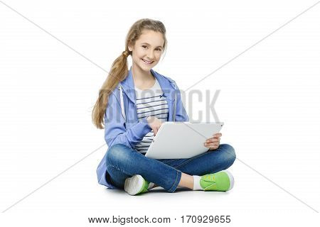 Beautiful teen age girl in casual clothes sitting on floor with big electronic tablet. Isolated on white background.