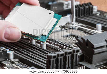hand holding a CPU and inserts it into the motherboard. focus on cpu