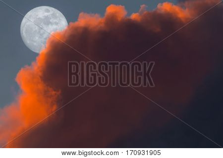 Full Snow Moon Rise peeking behind pink clouds during sunset