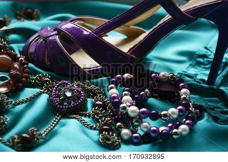 beautiful women's jewelry with stones on a contrasting background and a women's Shoe