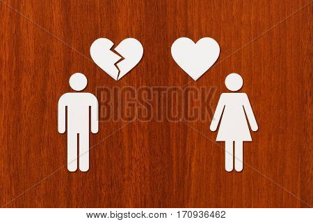 Paper woman with heart and man with broken one on wooden background. Unrequited love or divorce concept. Abstract conceptual image