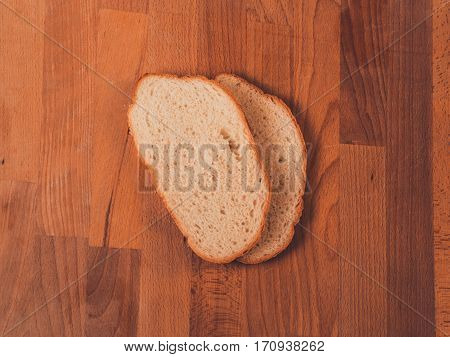 White bread on a wooden table. Top view. Fresh fragrant crispy sliced bread. Loaf of white bread slices on cutting board closeup. Home-made bread on a wooden background.