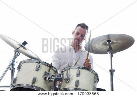white drummer behind drum set wears white shirt and plays the drums in studio smiling