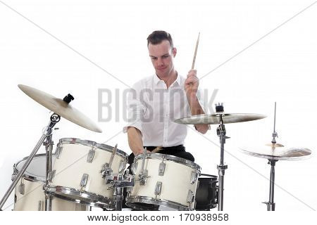 white drummer behind drum set wears white shirt and plays the drums in studio