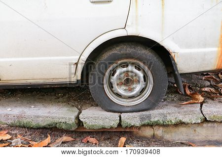 Close up wheel flat tire of the car old and cracked on the road