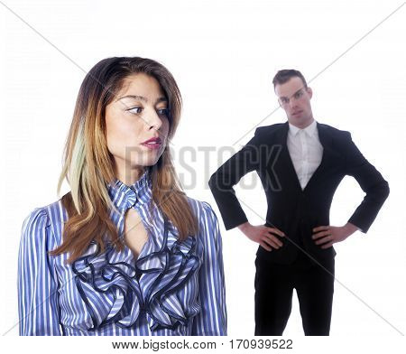 female subordinate worries anxiously while male boss stands in background with adamant gesture