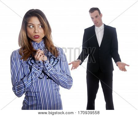 female subordinate worries anxiously while male boss stands in background with inquiring gesture