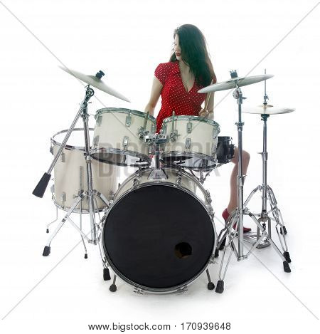 sexy brunette in red dress plays drum kit in studio against white background
