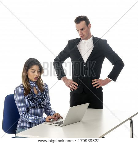 secretary works with laptop at table and boss is watching with unfriendly posture in studio with white background