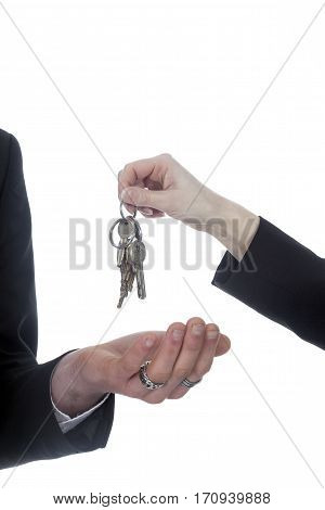 closeup of one hand with key ring hands over house keys to other hand against white background