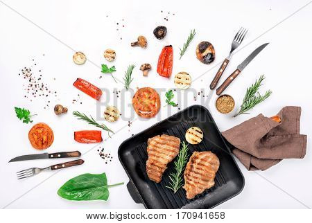Steak grill in the cast iron grill pan on a white background with a variety of grilled vegetables Top view. Flat lay