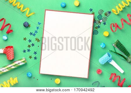 Blank card with different celebratory items on green background top view. Colorful celebration background. Flat lay