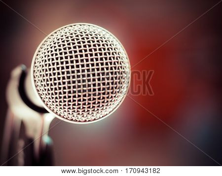 Close up of microphone in karaoke room or conference room. red background (microphone, karaoke, music )