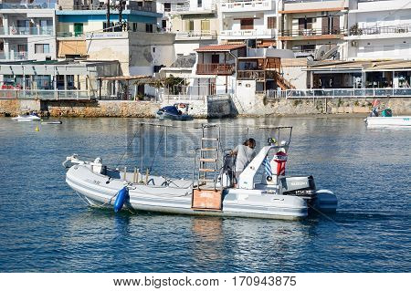 HERSONISSOS, CRETE - SEPTEMBER 17, 2016 - Rigid inflatable boat in the harbour with views towards waterfront restaurants Hersonissos Crete Greece Europe, September 17, 2016.