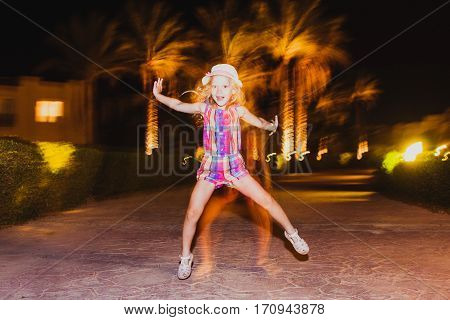 Little girl jumping and having fun. Summer night. Happy child. Motion photo. Active summer vacation on the beach.