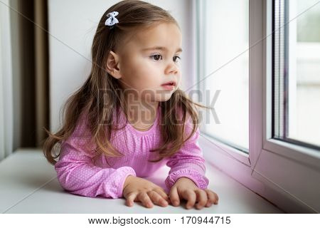 Cute little girl lying on the windowsill near the window