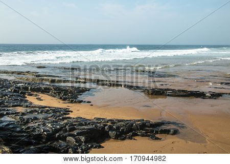 Rocks On Sea Shore Against Ocean And Blue Skyline