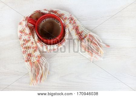 coffee in a red mug wrapped in a warm scarf knitted top view / soft warming drink