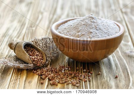 Buckwheat Flour In A Wooden Bowl And Scoop With Buckwheat.
