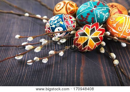 Easter eggs with willow twigs on a wooden plank table. The concept of the Easter holidays and folk art.