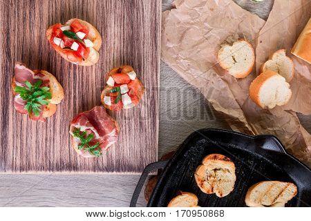 Toast On Grill Pan. Set Of Crostini With Tomato, Arugula, Prosciutto And Mozzarella. Italian Food, H