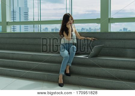 Beautiful Young Asian business women using smartphone and laptop computer sitting on the stairs with happiness and concentrate with city view background.