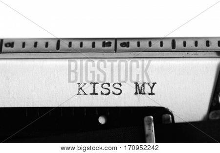 Typewriting on an old typewriter. Typing text: kiss my